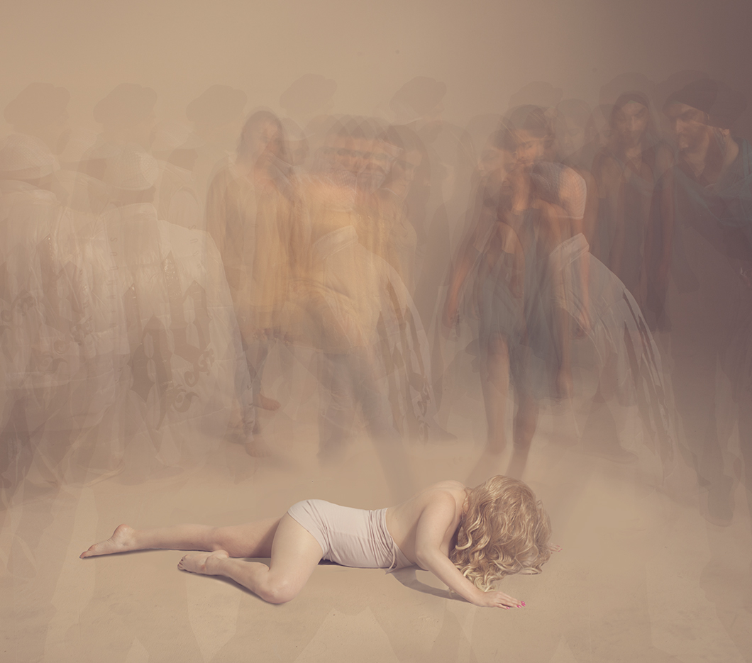 A woman lies on the ground surrounded by figures