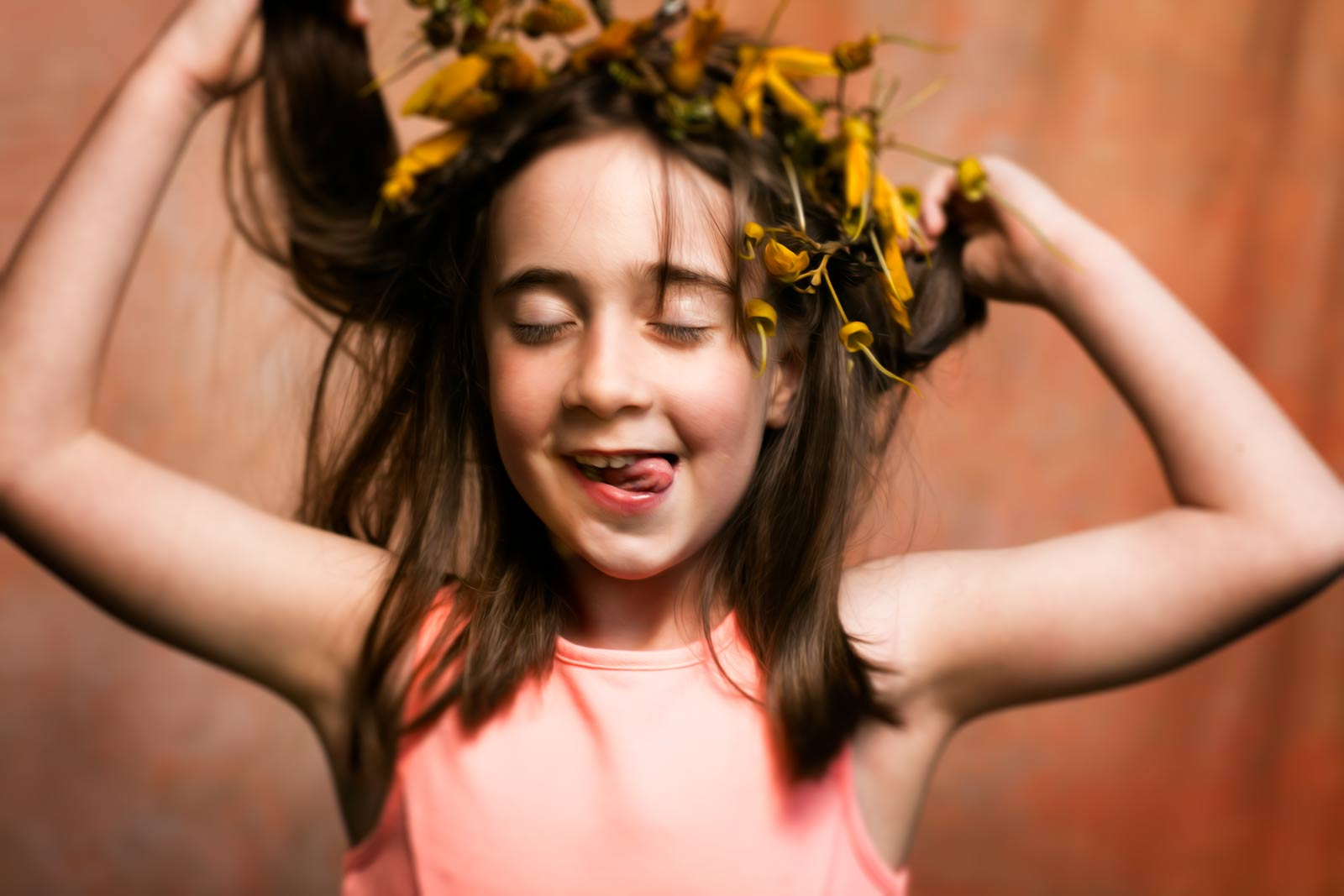little girl sticking out her tounge wearing a flower crown grinning with her eyes closed holding her hair